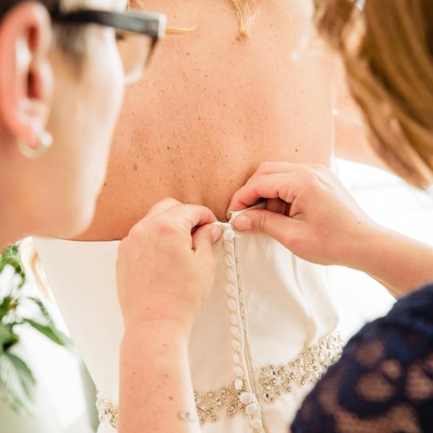 Trouwreportage bruid word aangekleed in haar trouwjurk in Lelystad